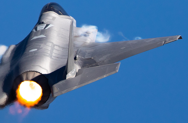 Extremely  close tail view of an F-35 Lightning II  in a high G turn, with afterburner on and  condensation trails at the wings root
